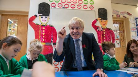 Prime Minister Boris Johnson looks at old photographs of London with students at Abbots Green Primar