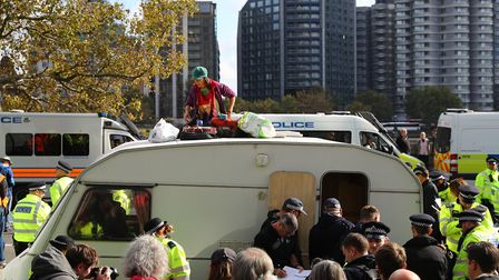 Extinction Rebellion protesters sit on top of a caravan outside MI5 Headquarters on Millbank in Lond