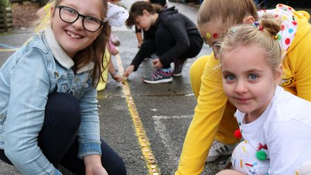 Autumn and Isla making penny lines in the playground at Martlesham primary for children in need Pic