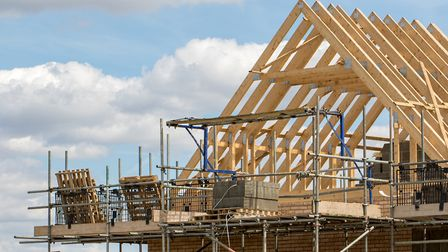 Construction industry. Timber framework of house roof trusses with scaffold on a building being buil