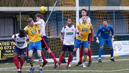 Billy Holland flicks on a corner kick whilst under pressure from Witham defenders. Photo: PAUL VOLLE