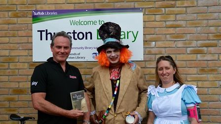 Alice and the Mad Hatter receive the book from Hughes. Picture: SUFFOLK LIBRARIES