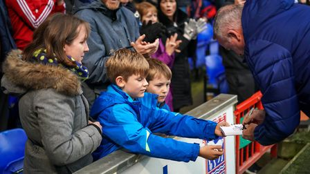 Town manager Paul Lambert signing autographs for young fans ahead of the game.Picture: Steve Wall