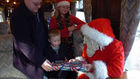 The Santa special at Colne Valley Railway. Father Christmas gives out present abord the train. P