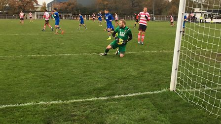AFC Sudbury keeper Paul Walker holds onto another Kingstonian effort, during a busy half for the cus