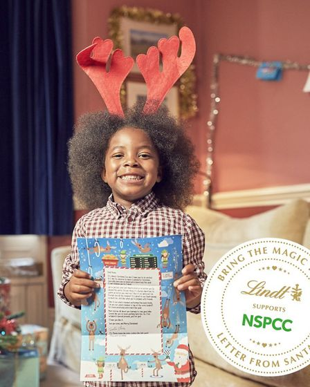 A little girl with a letter from Santa Picture: NSPCC