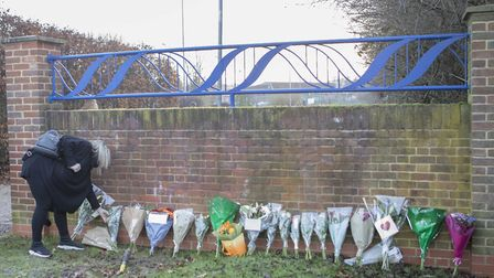 A woman lays flowers at the entrance to Debden Park High School, in Loughton, Essex Picture: RICK FI