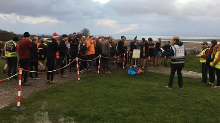 A field of 101 runners and walkers congregate in the cold and wet before the start of last Saturday'