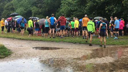 Runners congregate for the run briefing, in the shelter of the trees, before a very wet Wimbledon Co