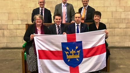 Suffolk's seven Conservative MPs with the St Edmund's flag at Westminster. Back row: James Cartlidge