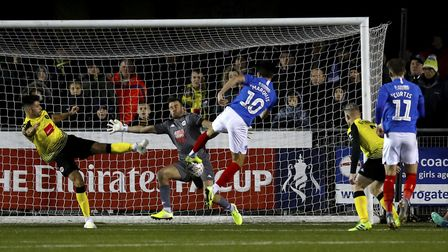 Portsmouth's John Marquis has a shot on goal saved by Harrogate Town goalkeeper James Belshaw in the