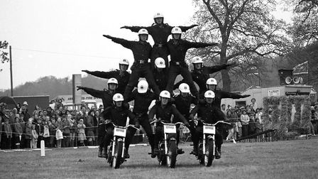 A group of talented motor bike performers balance in a pyramid in the main ring at the Hadleigh show