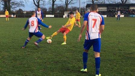 Ryan Clark (yellow shirt) competes for the ball with Clacton's Charlie Thompson. Clark netted a fine