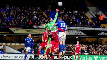 Gillingham keeper Jack Bonham punches clear as James Norwood looks to get his head on the ball.Pi