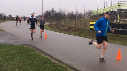 Runners approach the finish to the Cyclopath parkrun, on the road bike track in Gravesend on NYD. Pi