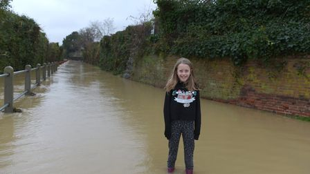 Alice Rutland standing in the flooded road in Coddenham Picture: SARAH LUCY BROWN