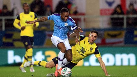Raheem Sterling (left) scored twice as Manchester City knocked Oxford United out fo the League Cup a
