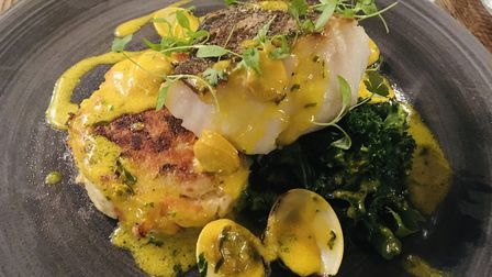 Cod with buttered greens, potato cake and clam and saffron sauce at The Angel, Wangford Picture: Ch