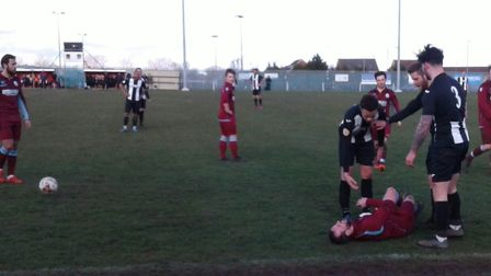 Woodbridge Town players stand over Sam Bond, annoyed that the Thetford defender made the most of a h