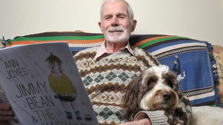Ron with his dog Morgan and a copy of Ann's childrens book Picture: SARAH LUCY BROWN
