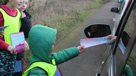 Jude hands an anti-idling leaflet to a driver, watched by fellow students Layla and Felicity. Pictur