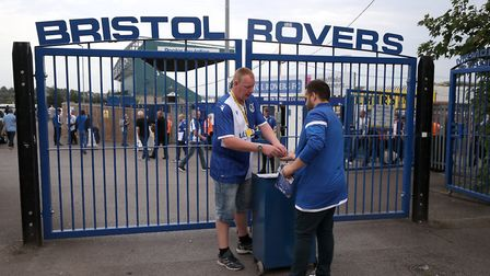 Outside the gates of the Memorial Stadium, a fan buys a matchday programme. Picture: PA SPORT