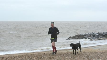 A dog walker braces the wind at Felixstowe beach Picture: SARAH LUCY BROWN