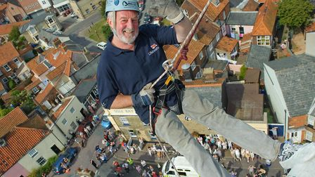Bernard Hill waves to the crowd asa he descends at the RNLI Southwold abseil on the lighthouse in th