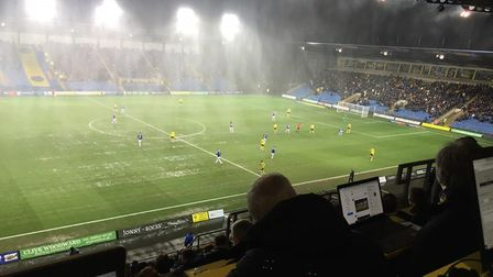 The wet and windy conditions under the floodlights at the Kassam Stadium, from the press box, when I