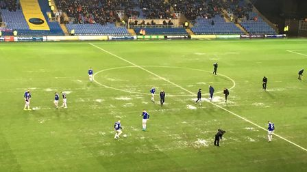 Ipswich Town players stay on the pitch during the break for play, because of the wet conditions. Pic