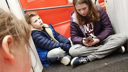 Florence, Sebastian and Evie Liddle had to sit on the floor outside a toilet on a crowded train Pict