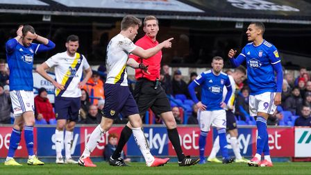 Rob Dickie points the finger at Kayden Jackson after referee Scott Oldham had shown the Ipswich plye