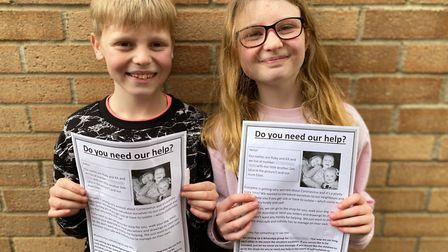 Kit, aged ten, and Ruby, aged 12, with their posters for the neighbours. Picture: ELLEN WIDDUP
