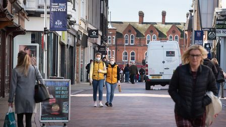 People in face masks walk through Ipswich town centre. Now people are being told to stay indoors