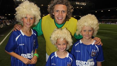 Jimmy Bullard meets young fans wearing replica wigs that were on sale at Planet Blue. Photo: Action