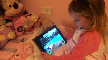Little girl watches as grandfather reads her a bedtime story remotely using an app. Picture: NATALIE