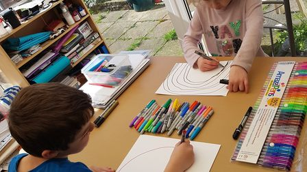 Tayla, six, and Zak, eight, making rainbows while being taught at home during the coronavirus lockdo