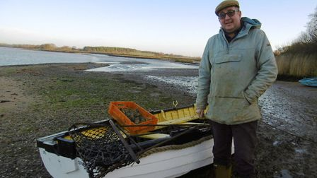 Jonathan Simper on the foreshore, with oysters harvested from the River Deben