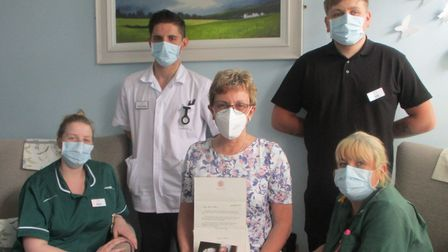 Sue Oates (centre), Barking Hall nursing home manager with the letter from one of the Queen's ladies