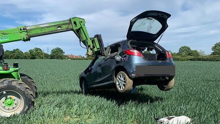 A farmer assisted police by lifting the damaged car to the nearby road using machinery. Picture: ESS