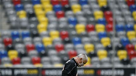 Fortuna assistant coach Rob Kelly wearing a face mask in front of the empty stands Picture: AP