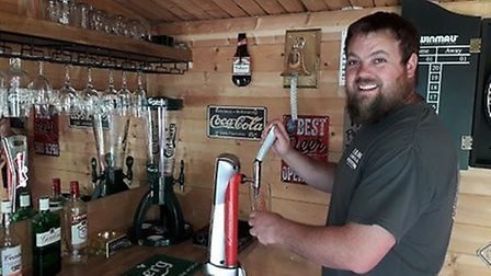 Michael, 34, pulling a pint in his new local pub in his very own garden. Picture: MICHAEL THOROUGHG