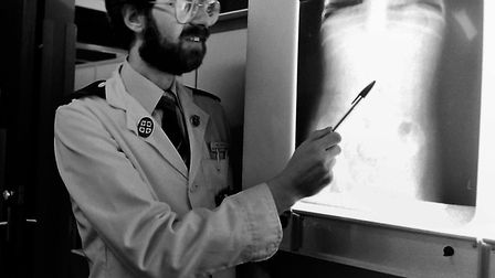 Black and white shots taken in January 1997 show Nigel Beeton examining X-ray images on a viewbox at