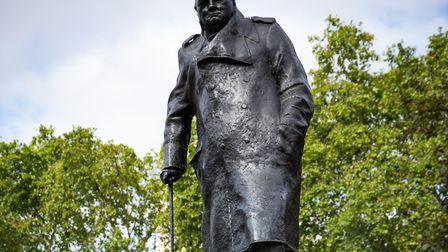 A worker cleans graffiti from the plinth of the statue of Sir Winston Churchill at Parliament Square