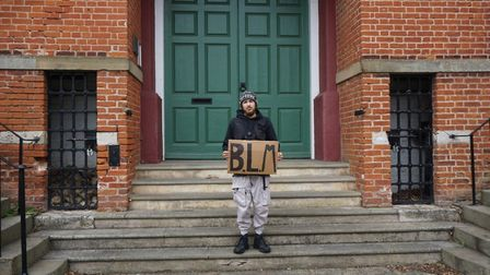 Harry Raithatha with one of the signs he posted on the Shire Hall in Woodbridge Picture: HARRY RAIT