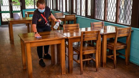 A table is wiped clean at a restaurant ahead of the lifting of further lockdown restrictions on Satu