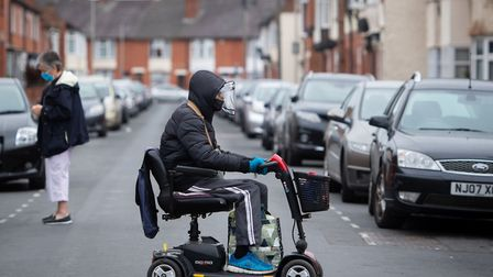 A man wearing a protective visor crosses the road on mobility scooter in Leicester as the city becam