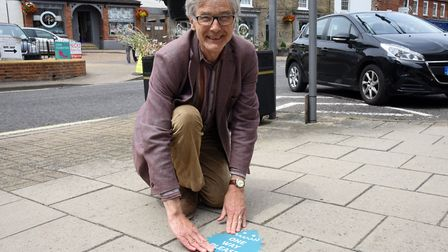 Jeremy Smith Chairman of Saxmundham town council putting hedgehog social distance signs in place P