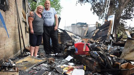 Bec Drake and her husband Colin amongst the remains of the burnt out workshop where the fire is thou