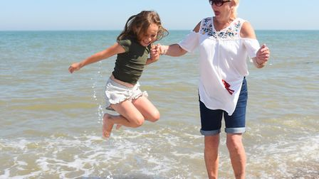 Seven-year-old Skyla Carter jumps the waves with her step-grandmother Sandy Buxton, from Great Yarmo